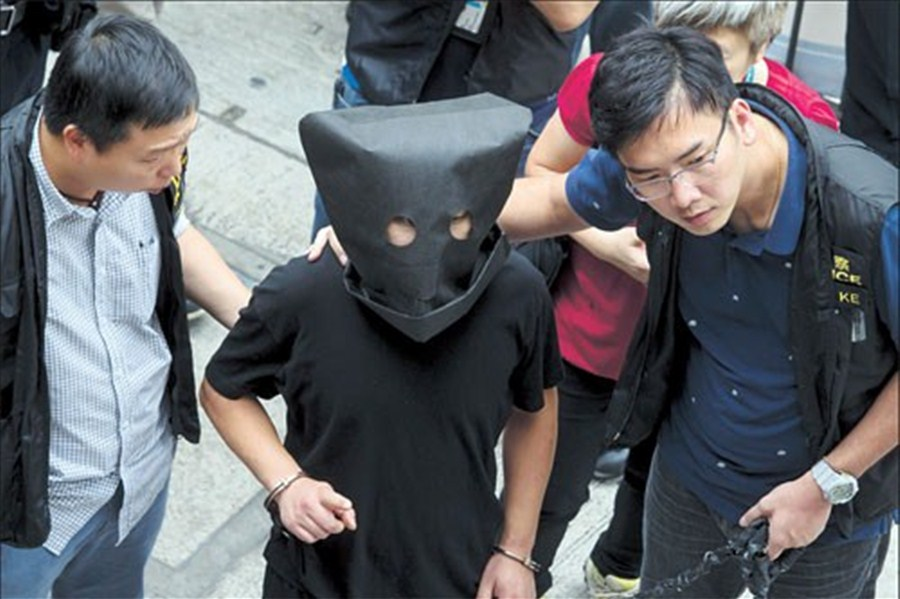 Police officers escort a man (center), suspected of involvement in the  kidnapping of a tycoon's granddaughter, for investigation in Hong Kong's  Choi Hun MTR ...